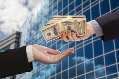 Male Hand Handing Stack of Cash to Woman with Corporate Building. Stock Photos