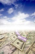 Stacks of Money, Sunburst and Blue Sky Stock Photos