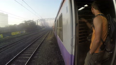 Man standing by open train door and watching landscape during ride. Stock Footage