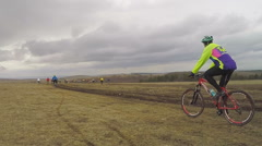 EDITORIAL. Young Bicycle Riders Moving In Field At Dull Day - stock footage