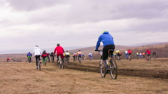 EDITORIAL. Group Of Young Bicycle Riders Moving In Field At Dull Day - stock footage