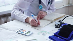 Doctor Hands in White Uniform Writing Prescription to a Patient Stock Footage