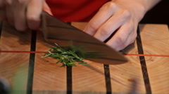 chopping herbs rosemary on butcher block - stock footage