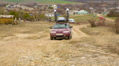 EDITORIAL. Car Of Technical Support With Bikes On Top Moving In Field Stock Footage