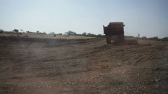 Truck reversing construction site, long shot Stock Footage