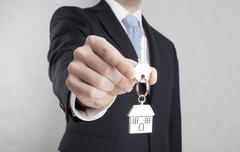 House key in businessman hand with clipping path - stock photo