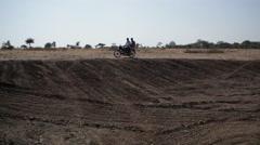 2 men driving motorbike on dry land, India, long shot Stock Footage