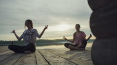 DOLLY MOTION: Two Young woman doing yoga near lake outdoors, meditation. Sport Stock Footage