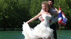 European bride holds wedding dress tain  looks at it against mangrove trees Stock Footage