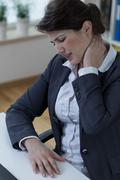Overworked businesswomen suffer from pain - stock photo