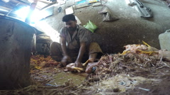 Man cleaning dead feathery animal in workshop in Mumbai. Stock Footage