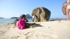Bride and groom stand by cliff with bouquet at foreground Stock Footage