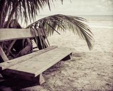Wooden bench on tropical beach, color filter applied - stock photo