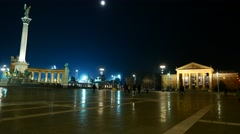 Pedestrians and traffic pass by on the Heroes Square in Budapest at night Stock Footage