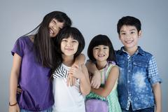 Stock Photo of Group of Happy asian child on gray background