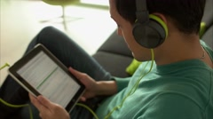 Asian Man Listening Music Podcast On Tablet PC With Earphones Stock Footage