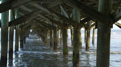 Waves roll in under pier in Myrtle Beach Stock Footage
