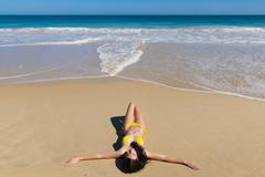 Girl in Yellow Bikini Relaxes on Summer Beach Stock Photos