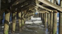 Long shot between pilings of pier in Myrtle Beach Stock Footage
