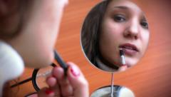 Beautiful young woman paints lips with lips brush before a mirror and sends Stock Footage