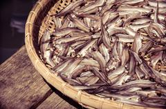 Small Fish drying on bamboo basket in the sun, color filter applied - stock photo