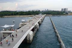 People jog and cycle on the bridge of Marina Barrage - stock photo