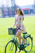 Young woman in short colorful dress with long hair rides a bicycle with baske Stock Photos