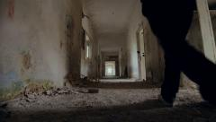 Hooded,troubled young man in wrecked abandoned building walking away Stock Footage