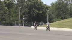 Small children on park alley riding bikes, sunny summer day for outdoor activity Stock Footage