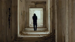 Hooded,troubled young man in wrecked abandoned building walking away slow motion Stock Footage