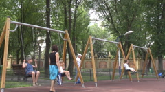 Parents supervise children when play in swing happy childhood memories park view - stock footage
