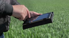 Hand near tablet PC on cereal field Stock Footage