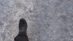Man winter boots walking on frozen sidewalk, moving feet view from above Stock Footage