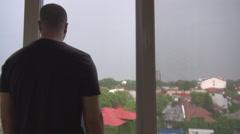 Man looking through the window in neighborhood houses, tallest building around Stock Footage