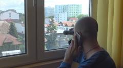 Stalking people from window, man using binoculars and having phone conversation Stock Footage