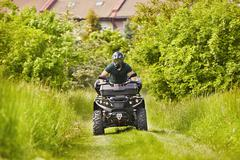 Man in helmet is driving the all terrain vehicle in nature near city. - stock photo
