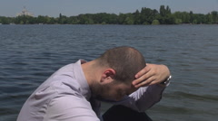 Upset depressed thoughtful businessman sitting alone in park, watching the lake Stock Footage