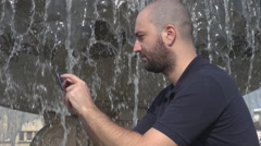 Handsome young businessman outdoors, sliding smartphone touchscreen, waterfall Stock Footage