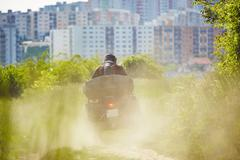 Man in helmet is driving the all terrain vehicle in nature near city. Stock Photos