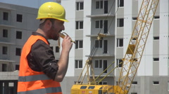 Construction worker wearing safety helmet eating banana in lunch time, sunny day Stock Footage