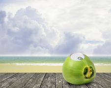 Stock Photo of Fresh coconut with can open tool on top and sea background