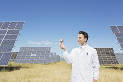 Scientist examining sphere by solar panels Stock Photos