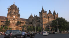 Traffic drives past the impressive Victoria Terminus in Mumbai Stock Footage