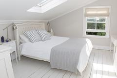 Bed in whitewashed attic bedroom Stock Photos