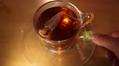 Pulling teabag out of glass Stock Footage