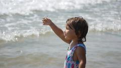 Man taking photo of cute child showing sea star on the beach. Slow motion - stock footage