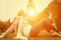 Happiness Woman seating on the grass in Paris under sunlight Stock Photos