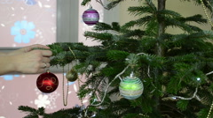 Girl hang decorative toy ball on Christmas tree branch Stock Footage