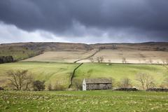 Clouds gathering over rural fields - stock photo