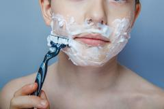 the boy of the European appearance decade person shaves, shaving - stock photo
